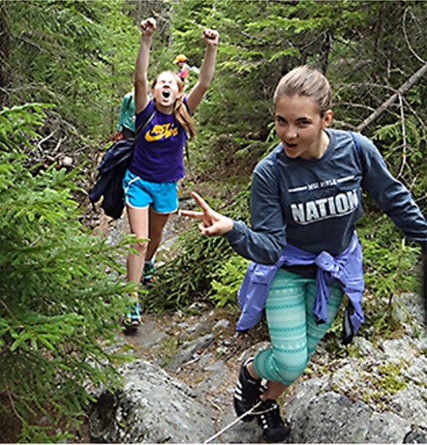 Teens hiking, with one giving the peace sign.