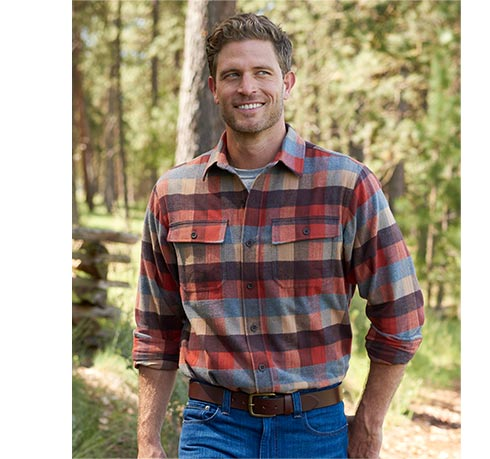 Smiling man in Chamois Shirt walking in woods.