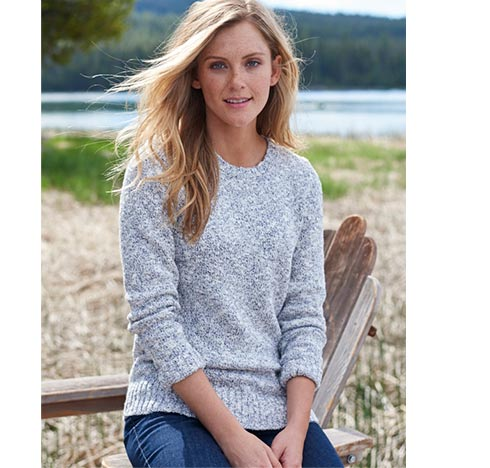 Woman leaning on chair by the water in Cotton Ragg sweater.