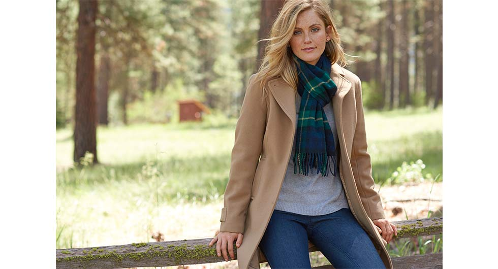 Woman leaning on wooden fence in fall clothing.