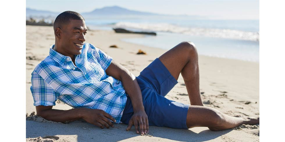 Iimage of man on beach in linen shirt.