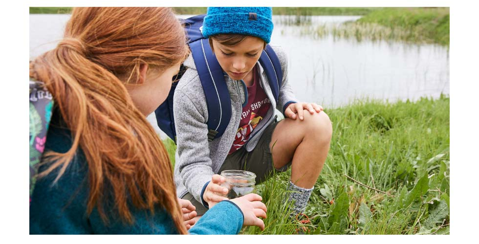 Kids with L.L.Bean packs outside collecting frogs