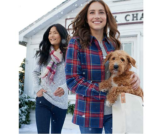 Women in L.L.Bean shirts and sweaters shopping with puppy in snow.