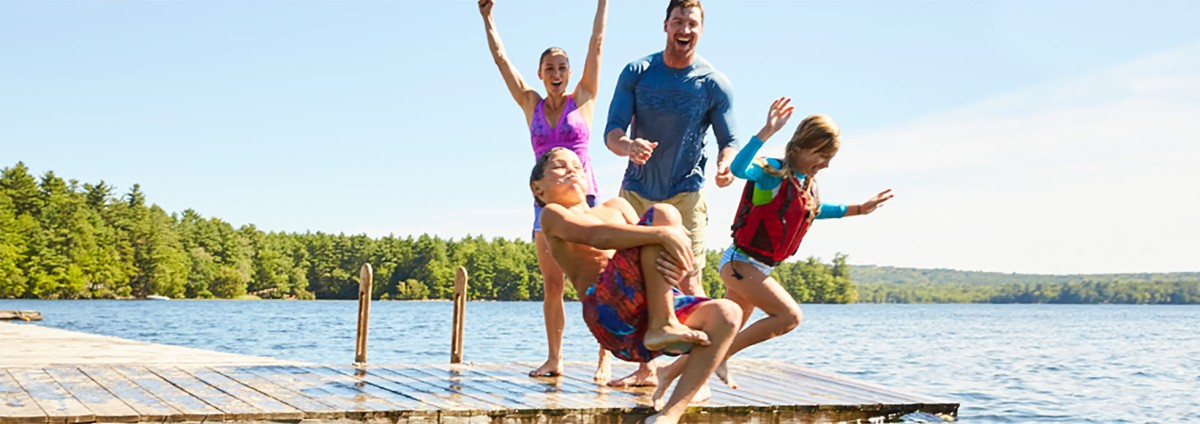 Family jumping off a dock into the water.
