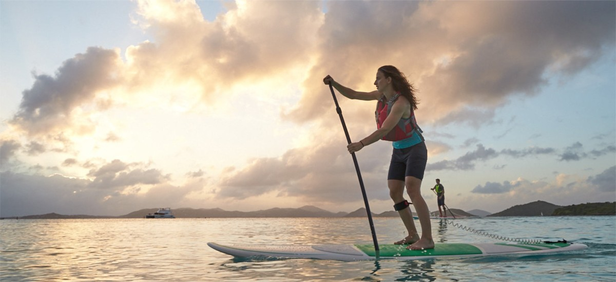 Woman paddling a stand up paddle board in front of a sunset.