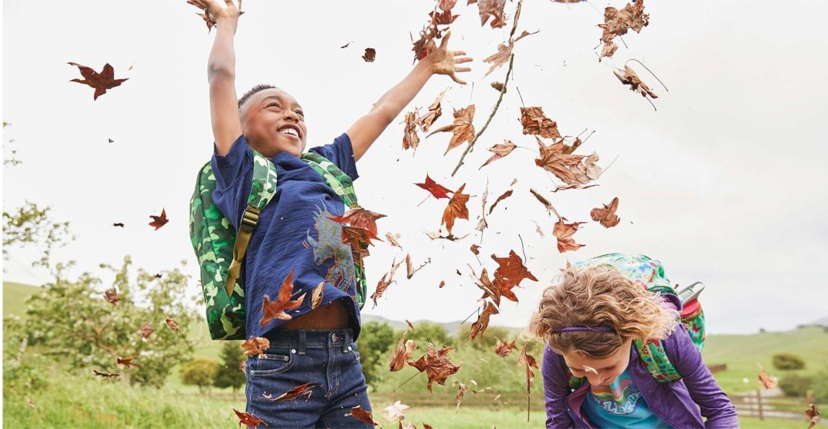 kids throwing leaves in air wearing L.L.Bean backpacks