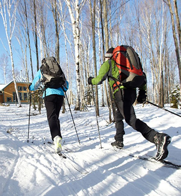 Two people cross-country skiing to a backcountry hut.