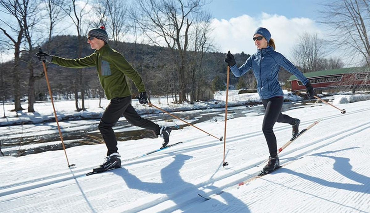 Two people cross-country skiing at a nordic ski center.