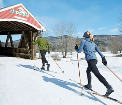Two people skiing towards a covered bridge at a nordic ski center.
