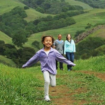 A child running ahead of her parents, walking in a hilly green valley.