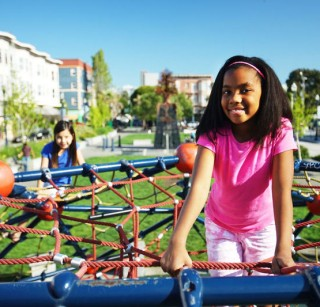 A smiling girl sitting on top of a climber in a city park