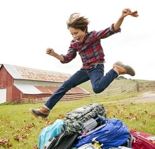 Boy Jumping over backpacks