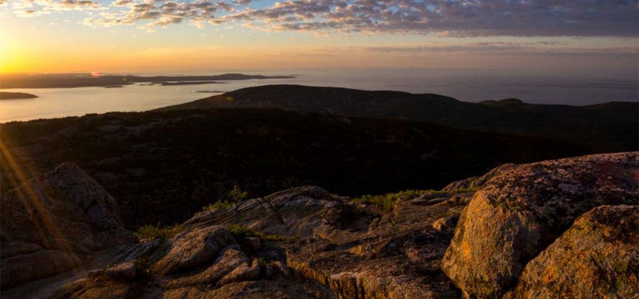 Beautiful panoramic view of a sunset over a large body of water from a rocky hillside.