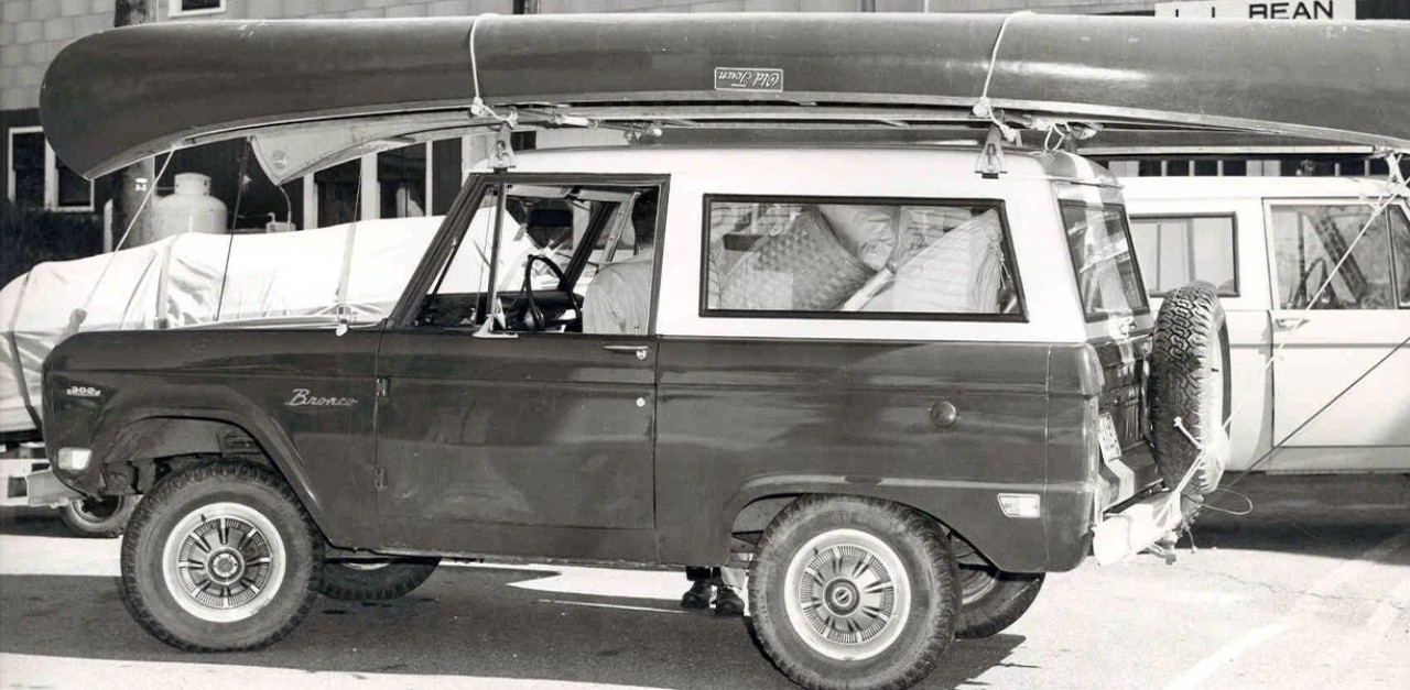 A black and white 1942 photo of a Ford Bronco packed to the brim with camping equipment, a canoe strapped to the top.