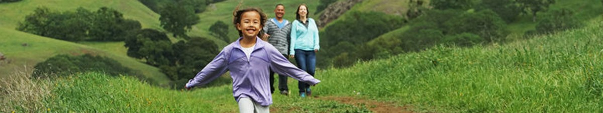 Girl running in a green field with parents walking behind her.