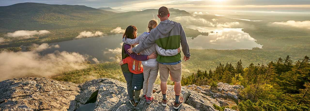 Family, arm in arm, enjoying the view from a mountaintop.